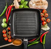 Cast iron griddle pan on black background with vegetables