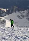 Snowboarder On Off-piste Slope In Sun Evening