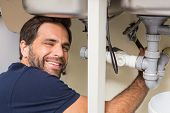 Happy plumber fixing under the sink in the kitchen