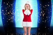 Pretty santa girl with hands on face against glittering screen on black background