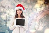 Festive brunette holding a tablet pc against light glowing dots design pattern