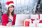 Festive brunette shopping online with laptop against glittering lights in room