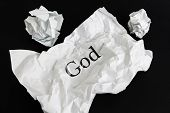 Crumpled Paper Sheet With Word God Isolated On Black