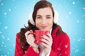 Woman in winter clothes enjoying a hot drink against blue vignette