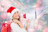 Festive blonde holding megaphone and bags against light glowing dots on blue