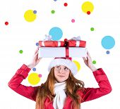 Festive redhead holding pile of gifts against dot pattern