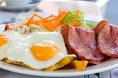Fried eggs with bacon and salad