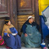 LA PAZ, BOLIVIA, MAY 8, 2014:  Local women in traditional attire sit on doorstep
