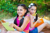 Hispanic Sisters Reading In Summer Park