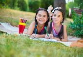 Hispanic Sisters Drawing In Summer Park