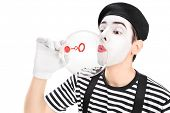 Mime artist blowing a bubble through wand isolated on white background