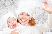 Selfie  In Winter. Happy Family Mother With Daughter And Photographed Self On  Mobile Phone