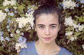 Portrait Of A Beautiful Teenage Girl In A Blooming Bush