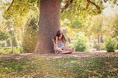 Teenage Girl Is Sitting And Relaxing Under A Big Tree In A Park