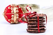 Chocolate cookies with red ribbon and christmas decoration in back