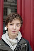 Portrait Of A Beautiful Teenage Boy In Front Of A Red Door