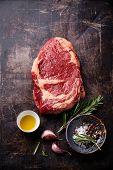 Raw Fresh Meat Ribeye Steak And Seasonings On Dark Background