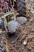 pic of plow  - Image from the back of a tractor plowing the land focus is on plow - JPG