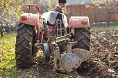 foto of plowing  - Senior farmer on an old red tractor plowing his garden in the backyard - JPG