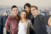 Selfie of four tourist on top of the famous tall building in New York City, with a great view over manhattan