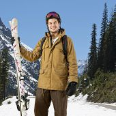 Smiling skier, wearing a helmet and goggles, with his skis in his hand posing on a beautiful day in a mountain landscape