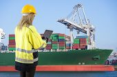 Female docker overlooking the unloading of a large container ship in an industrial harbor, carrying an electronic consignment note on her tablet