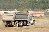 image of dump_truck  - Dump truck at a large construction site removing a hill during an airport runway expansion project - JPG