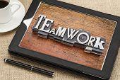 teamwork  word in vintage metal type printing blocks on a digital tablet with a cup of coffee