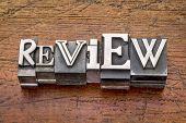 review word in mixed vintage metal type printing blocks over grunge wood