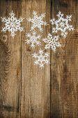White Snowflakes On Wooden Background. Christmas Decoration