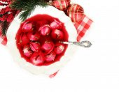 Traditional polish clear red borscht with dumplings and Christmas decorations isolated on white