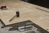 Close up of a workman's tools on a floor that is being tiled. More work in progress visible in backg