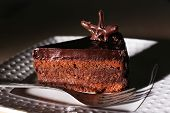 Delicious chocolate cake on plate on table
