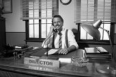 picture of 1950s style  - Smiling director working at desk having a phone call 1950s style office - JPG