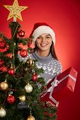 Young female with red giftbox looking out of decorated xmas tree