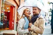Amorous valentines standing under umbrella in urban environment
