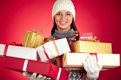 Portrait of smiling female holding stack of giftboxes