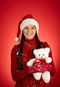 Portrait of happy girl in Santa cap holding fluffy teddybear