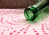 Bright green bottle on hue of pink flowing polka dots.