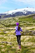 Sport athlete woman - exercising trail runner running. Active female fitness model training and jogging outdoors in beautiful mountain nature landscape by Snaefellsjokull, Snaefellsnes, Iceland.