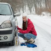 Woman putting winter tire chains on car wheel snow breakdown
