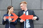 Business man and woman holding two big red arrows against each other