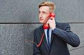 Business man making call with red phone on wall in a city