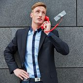 Business man making a call with a red phone taped to a wall
