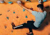 Man Climbing Up On Wall Indoors