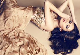 picture of studio  - fashion studio photo of beautiful young girl with dark hair wearing luxurious beige dresslying on the floor at studio - JPG