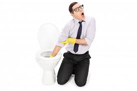 foto of disgusting  - Disgusted man cleaning a toilet with cleaning gloves isolated on white background - JPG