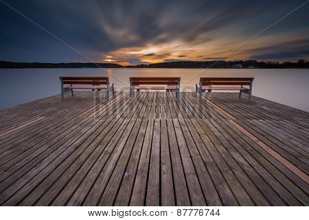 Beautiful Long Exposure Lake With Pier On Foreground And Bench.