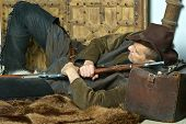 stock photo of bandit  - Bandit with gun in the wild west on carpet - JPG