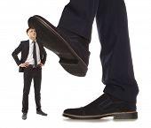 foto of big-foot  - Cared small businessman under big leg his boss - JPG